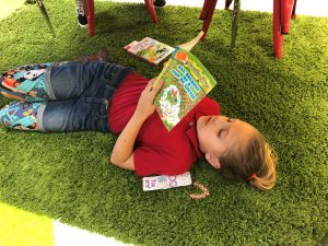 Young girl laying on carpet while reading a book in the media center
