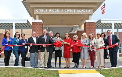 Administrators and community members standing in front of building at ribbon cutting